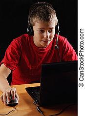 Teenager playing on laptop