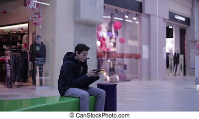 Teenager playing phone sitting on the bench