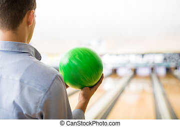 Teenager Playing With Green Bowling Ball In Club