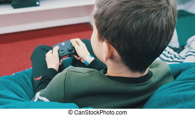 A teenager plays a game console with a joystick while sitting in a children's entertainment center. Back view of the child sits in a modern soft armchair and has fun playing modern games on a console.