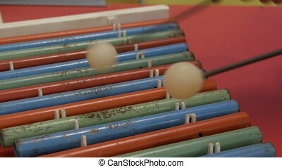 Teenager plays multi-colored musical instrument xylophone -...