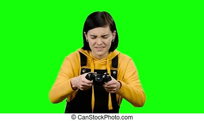 Teenager plays video games on the joystick. Green screen -...