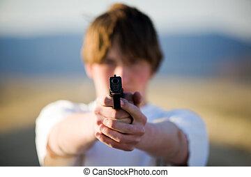 teenager pointing handgun at camera - teenager pointing...