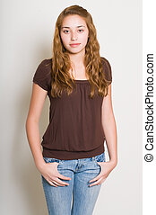 Pretty teenage girl in a brown blouse and jeans