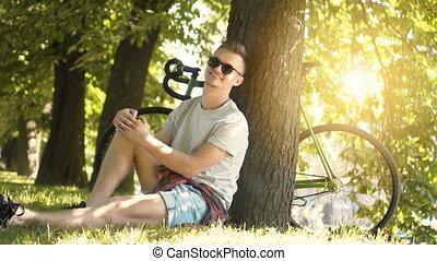 Teenager Rests in Park - Joyful teenager in black sunglasses...
