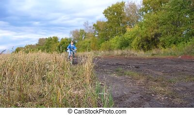Teenager riding a bike, doing sports in the fresh air. Travel and active entertainment