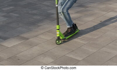 Teenager riding scooter sliding on pavement