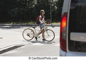 Teenager school girl with bike walk in pedestrian crossing in front of a car