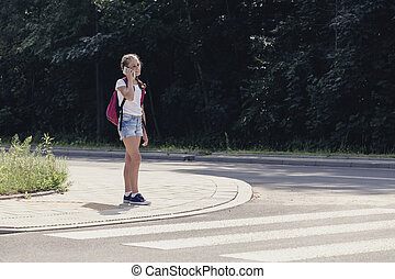 Teenager schoolgirl talking on the phone and walking in pedestrians crossing