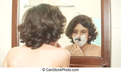Teenager shaves first time, teenage boy applying shaving...