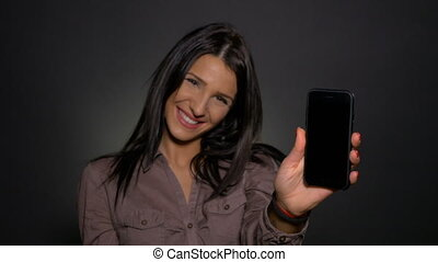 Teenager showing and presenting the screen of her smart phone to the camera