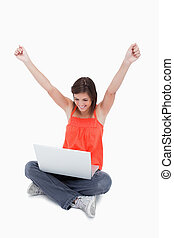 Teenager showing her satisfaction behind her laptop while...