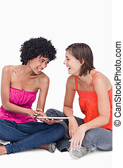 Teenager showing something on her tablet PC to her laughing friend