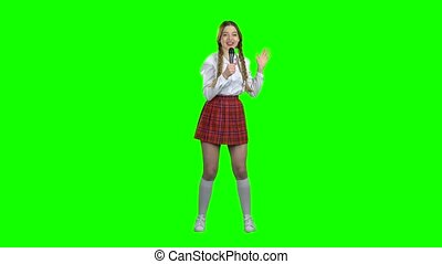 Teenager singer is singing a song. Green screen