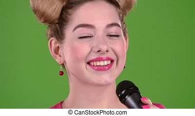 Teenager sings into the microphone. Green screen. Close up. Slow motion