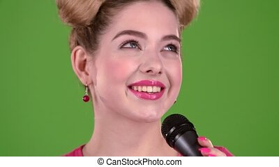 Teenager sings into the microphone. Green screen. Close up