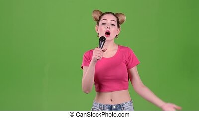 Teenager sings into the microphone. Green screen. Slow motion