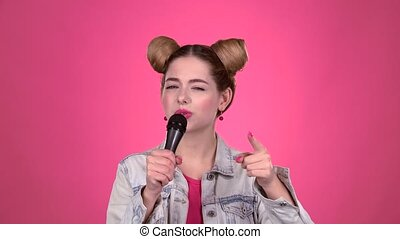 Teenager sings into the microphone. Pink background