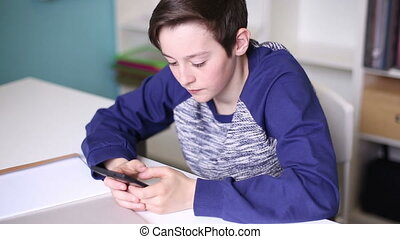Teenager sitting at a table playing on your phone - Teenager...
