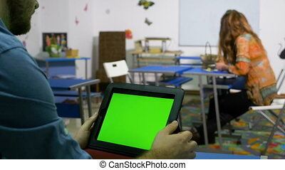 Teenager sitting at desk in a class room and swiping the display of a tablet pc