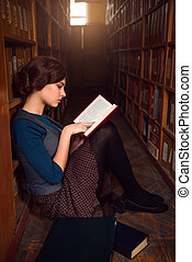 Teenager sitting on a floor of library and read.