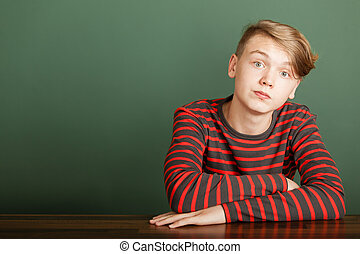 Teenager sitting on green background