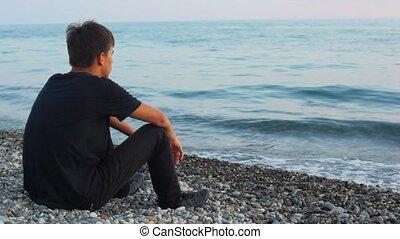 teenager, sitzt, auf, steinstrand, und, aussehen, meer,...
