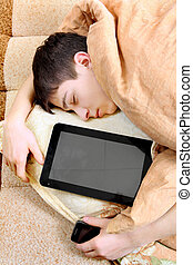 Teenager sleeps with Tablet Computer - Tired Teenager...