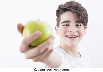 teenager smiling with braces and fresh green apple, dentures...