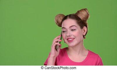 Teenager speaks by phone. Green screen