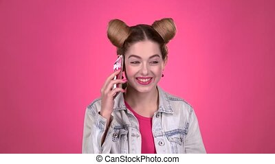 Teenager speaks by phone. Pink background