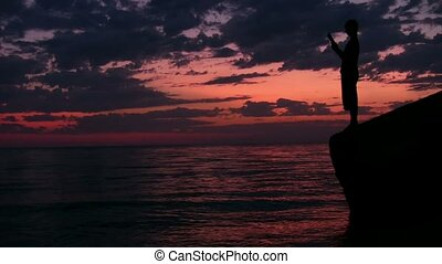 teenager stands on rock above sunset sea and reads