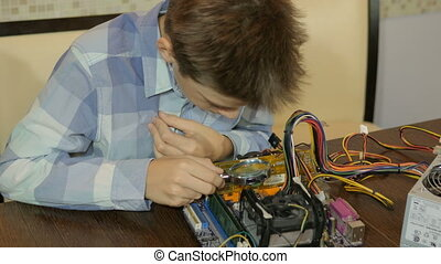 Teenager studying computer device. Adds RAM.