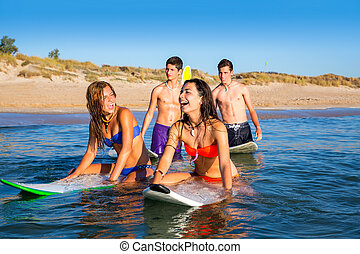 Teenager surfer boys and girls swimming ove surfboard - ...