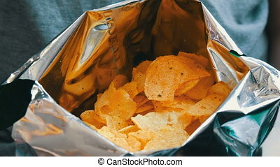 Teenager takes with the hands potato chips in packs -...