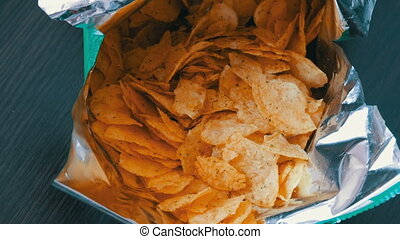 Teenager takes with the hands potato chips in packs