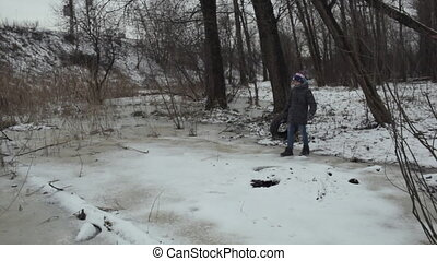 Teenager throwing used tire in winter park - Boy teenager...