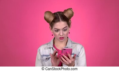 Teenager thumbs a photo on a smartphone. Pink background. Slow motion