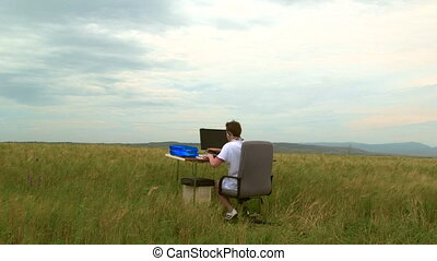 Teenager using desktop computer outdoors