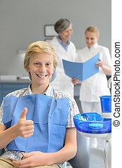 Teenager visit dentist at dental surgery thumbup