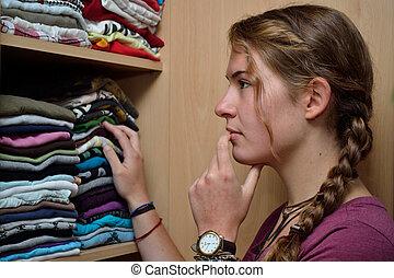 Teenager vor Kleiderschrank - Jugendliche sucht nach...