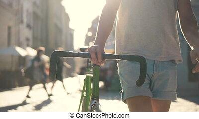 Teenager Walks with Bike in City - Medium-height teenager...
