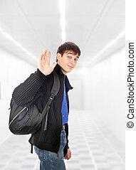 teenager wave goodbye in the white corridor