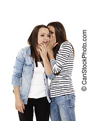 teenager whispering gossip to her sister on white background