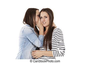 teenager whispering her sister in her ear on white background