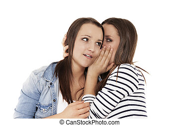 teenager whispering news to her sister on white background