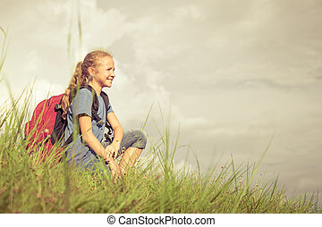 teenager with a backpack sitting on the grass