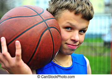 Teenager with a basketball on the court