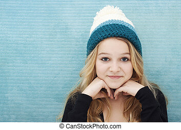 Girl with long blond hair and woolly cap space for text