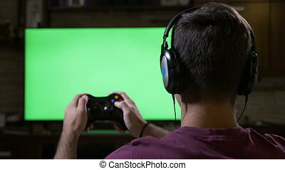 Teenager with earphones using game controller in front of...